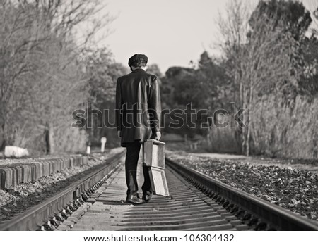 Young man with hat and old suitcase in rail way - stock photo