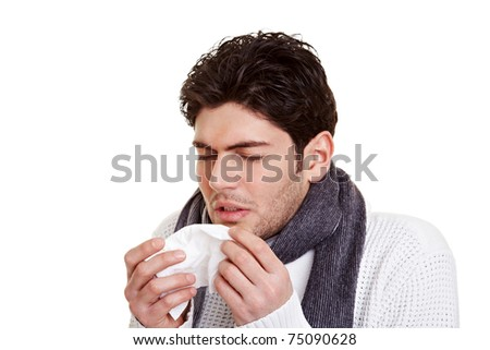 Young man with hay fever sneezing in a tissue