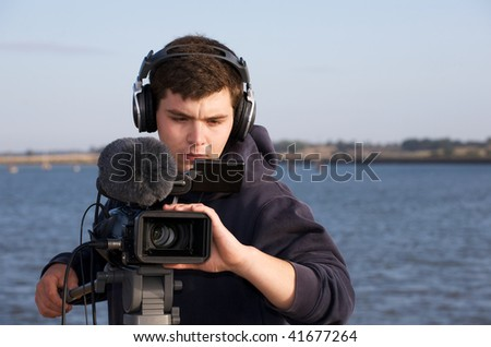 Young man with headphones and video camera - stock photo