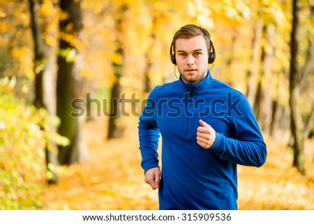 Young man with headphones jogging in autumn nature and listening music - stock photo