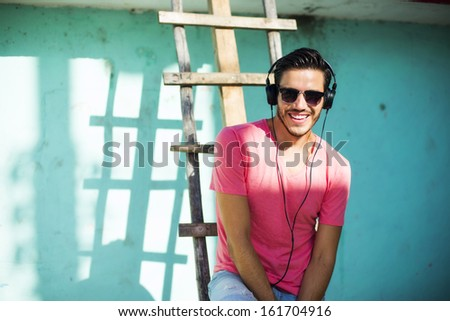Young man with headphones listening music on a urban background