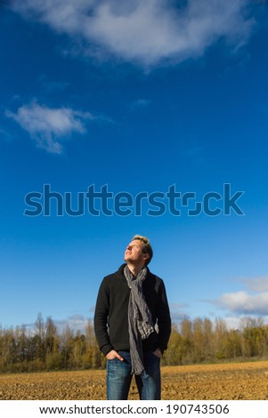 Young man with his face to the sun and eyes closed in a plowed field with trees and blue sky with clouds  - stock photo