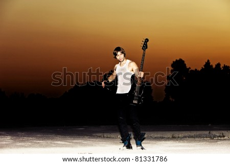 young man with his guitar at sunset, full body shot - stock photo