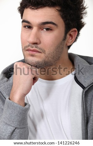 Young man with his hand on his chin - stock photo