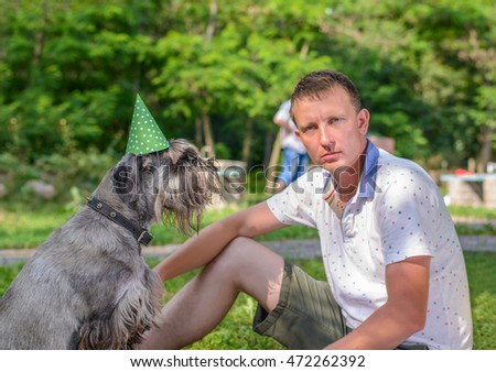 Young man with his pet dog in a green party hat sitting together on the grass in a park celebrating a special event