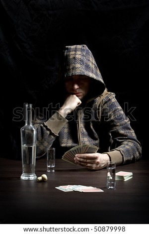 Young man with hood, drinking alcohol and gambling - stock photo