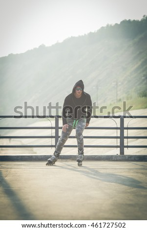 young man with inline skates ride in summer park outdoor roller skater