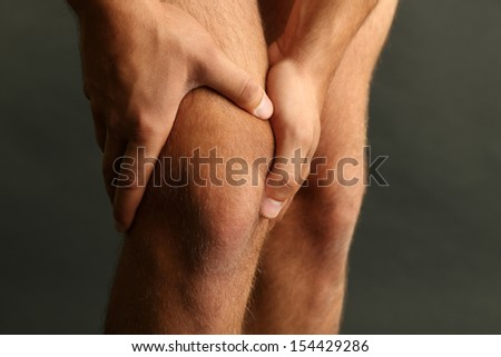 Young man with knee pain on dark background - stock photo