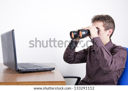 young man with laptop and binoculars searching for information
