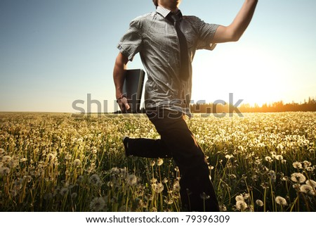 Young man with laptop in hand running on meadow with dandelions - stock photo