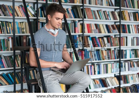 Young man with laptop in library