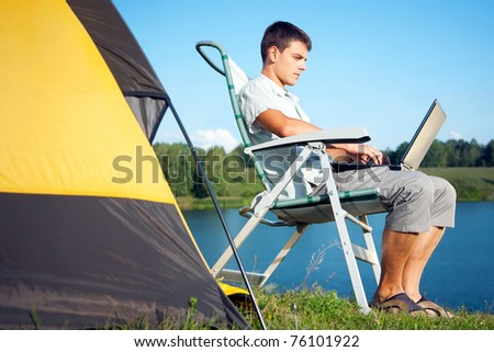 young man with laptop near the tent - stock photo
