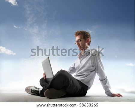 Young man with laptop on his knees - stock photo