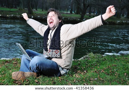 Young man with laptop outdoor - stock photo
