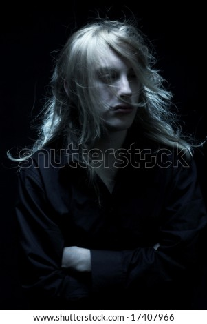 Young man with long blond hair. Romantic portrait.