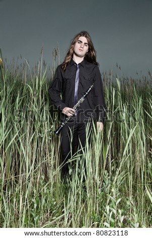 Young man with long brown hair wearing black suit holding clarinet in field of long grass. Stormy cloudy sky.