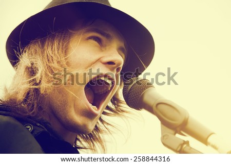 Young man with long hair and hat singing, shouting to microphone. Vintage, music, hipster.  - stock photo