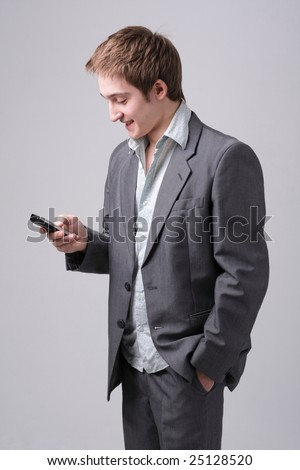 Young man with mobile phone standing against grey background - stock photo