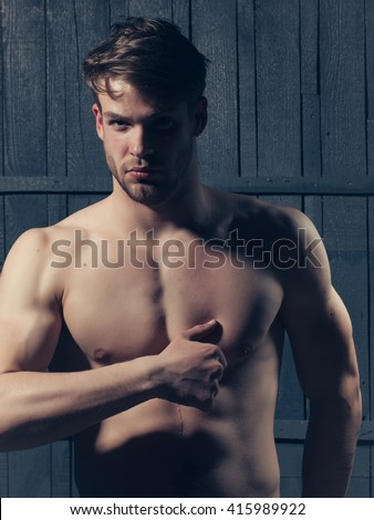 Young man with muscular bare torso and sexy body posing in studio on wooden background - stock photo