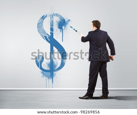 Young man with paint brush and banknote painted on the wall