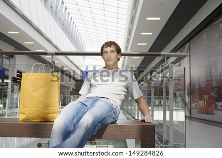 Young man with paper bag sitting on bench in shopping center - stock photo