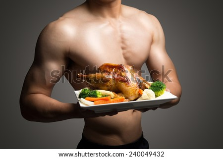Young man with perfect body holding and showing roast chicken for delicious menu,healthy food - healthy lifestyle concept ,clipping path  - stock photo