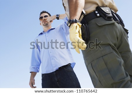 Young man with police officer from below - stock photo