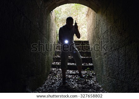 Young man with radio set and flashlight enters the stone tunnel - stock photo