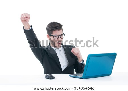 Young man with raised fists using laptop - stock photo