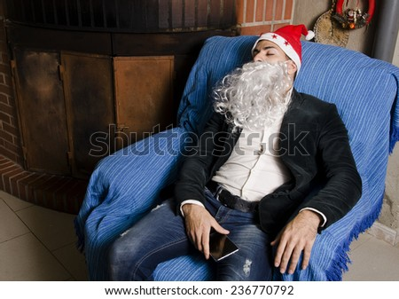 Young man with Santa Claus costume sleeping with possible hangover at sofa before christmas party - stock photo