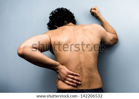 Young man with severe backpain from sciatica - stock photo