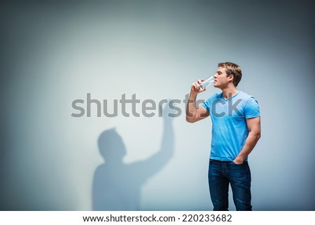 Young man with shadow in studio - stock photo