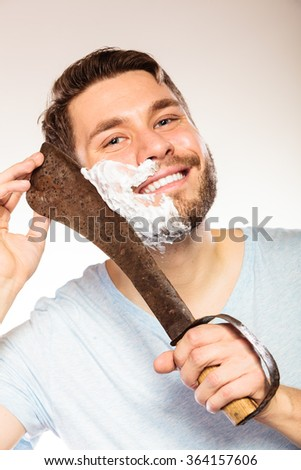 Young man with shaving cream foam on half of face having fun with machete large knife. Handsome guy removing beard hair. Skin care and hygiene humor. - stock photo