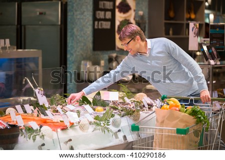 Young man with shopping cart - stock photo