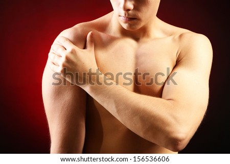 Young man with shoulder pain, on red background - stock photo