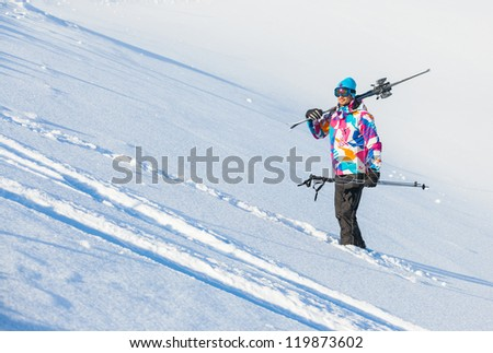 Young man with skis and a ski outfit walking in snow at winter outdoor in the Zillertal Arena, Austria - stock photo