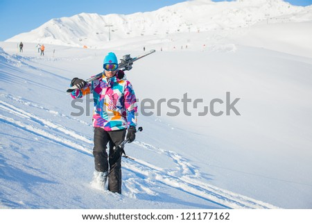 Young man with skis and a ski outfit walking in snow at winter outdoor. Tirol, Austria - stock photo