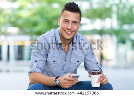 Young man with smartphone outdoors