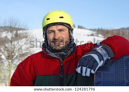 young man with snowboard clothes a helmet  in winter mountains