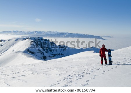 Young man with snowboard in Bucegi mountains, Romania