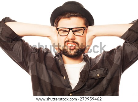 Young man with squares shirt covering his ears with his hands. Isolated on white. - stock photo