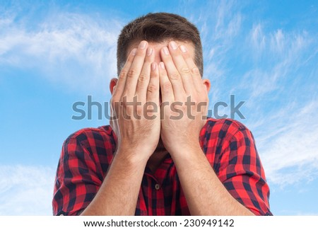 Young man with squares shirt over clouds background. Looking scared - stock photo