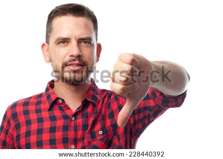 Young man with squares shirt over white background. With the thumb down