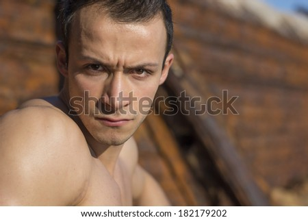Young man with stern severe eyes looking directly in camera. Outdoors shot