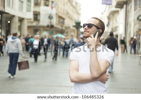 Young Man with sunglasses and mobile phone walking, background is blured city - stock photo