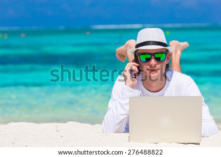 Young man with tablet computer and cell phone on tropical beach - stock photo