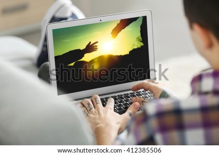 Young man with tattoo using laptop on a sofa at home - stock photo