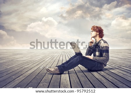 Young man with thoughtful expression sitting on a parquet floor and using a laptop - stock photo