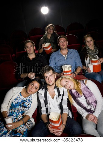 Young man with two women at the movie theater - stock photo