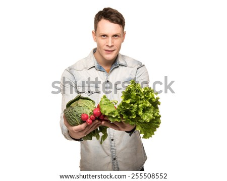 Young man with vegetables in front of him isolated on white
